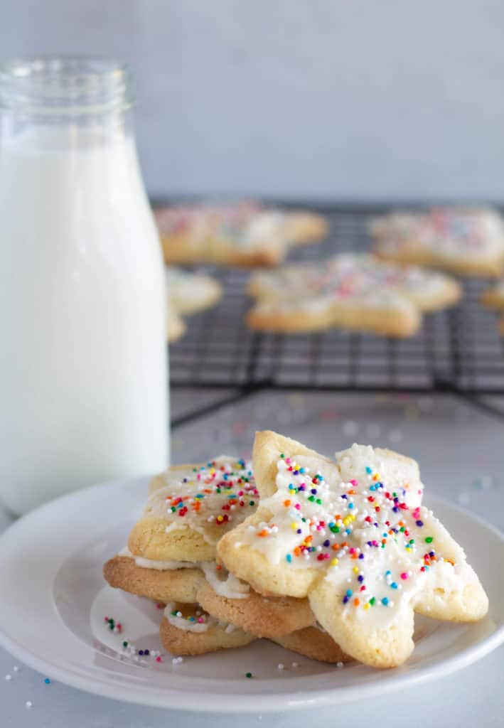 keto sugar cookies with sprinkles stacked on a white plate