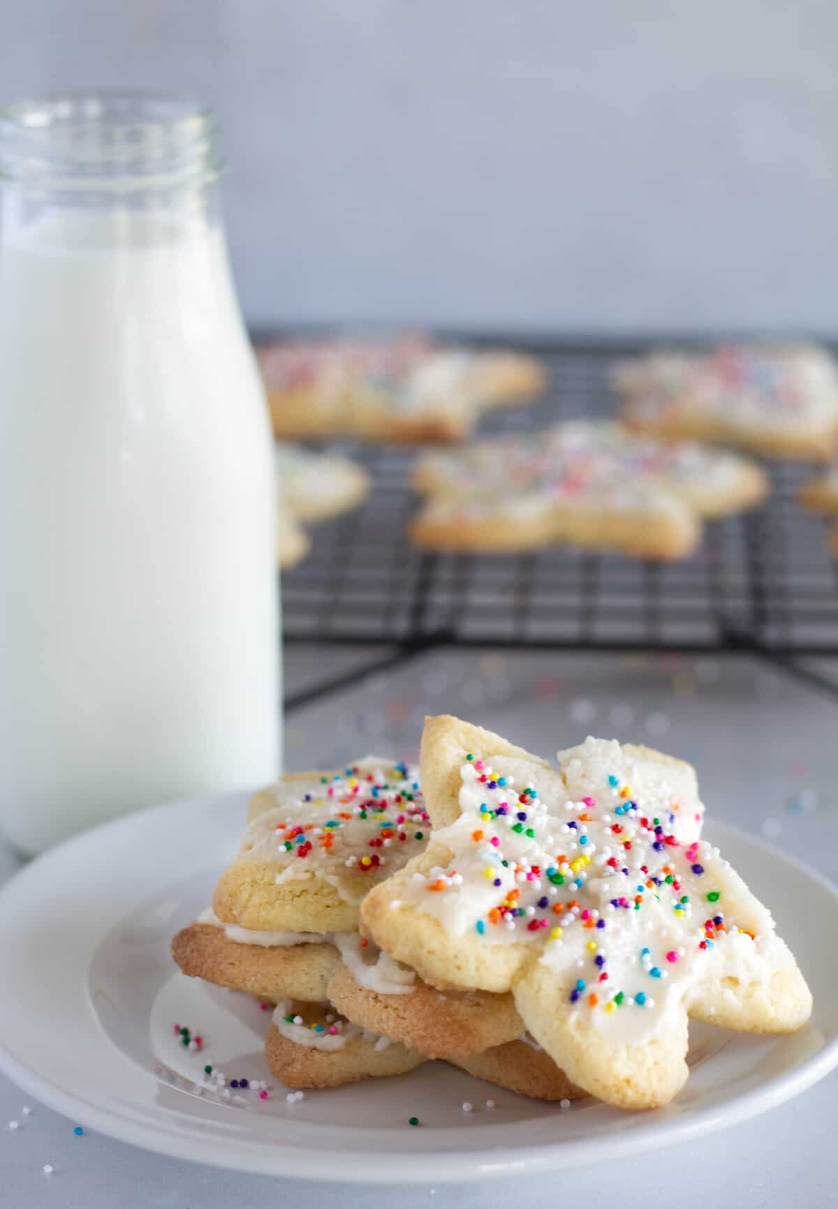 cookies with sprinkles stacked on a white plate