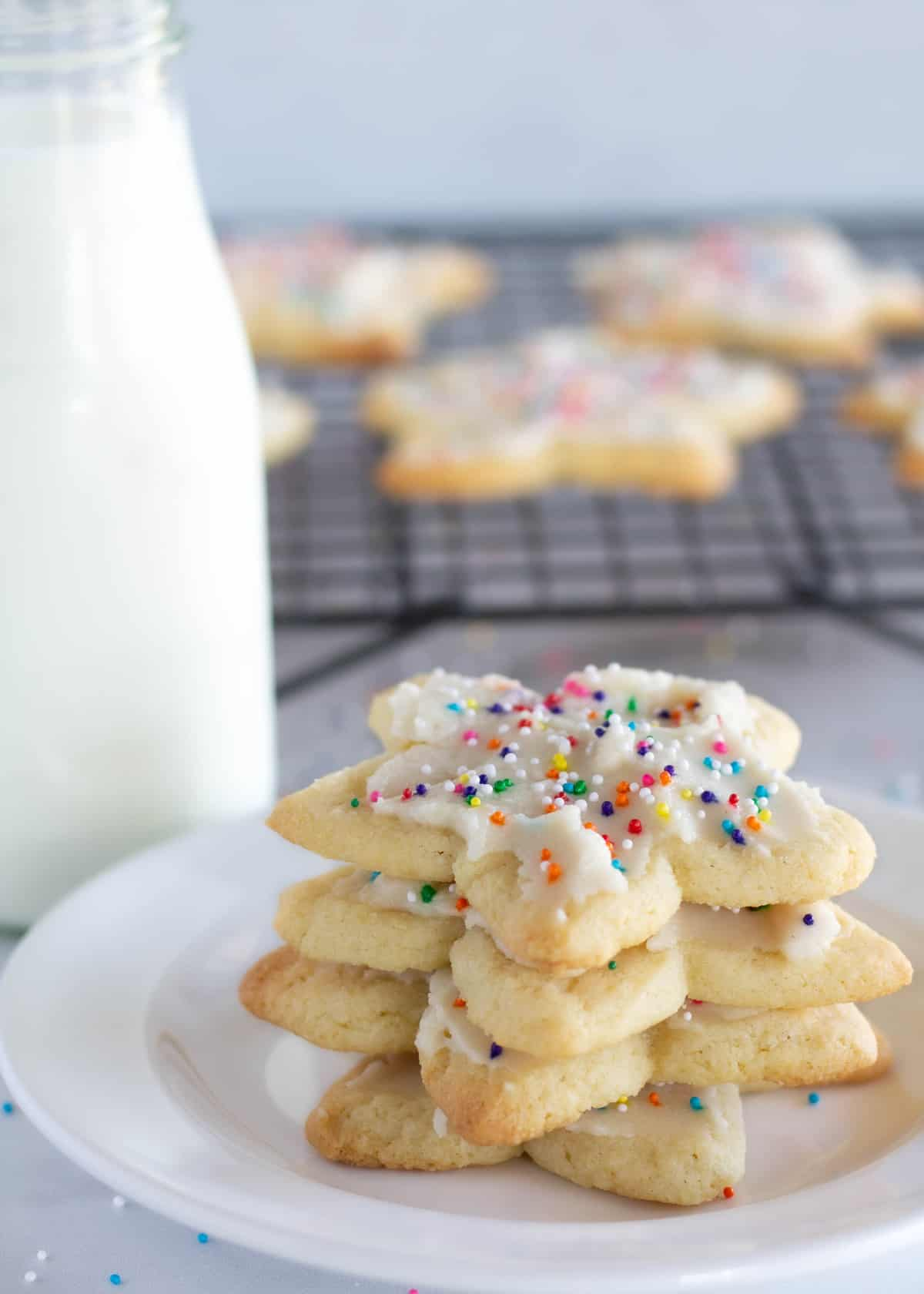 sugar cookies stacked on white plate with milk