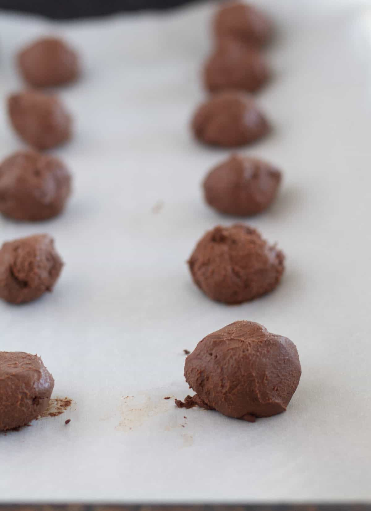 chocolate ganache rolled into balls on parchment lined baking sheet