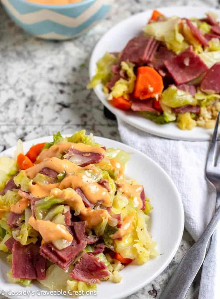 corned beef and cabbage on white plate with dressing