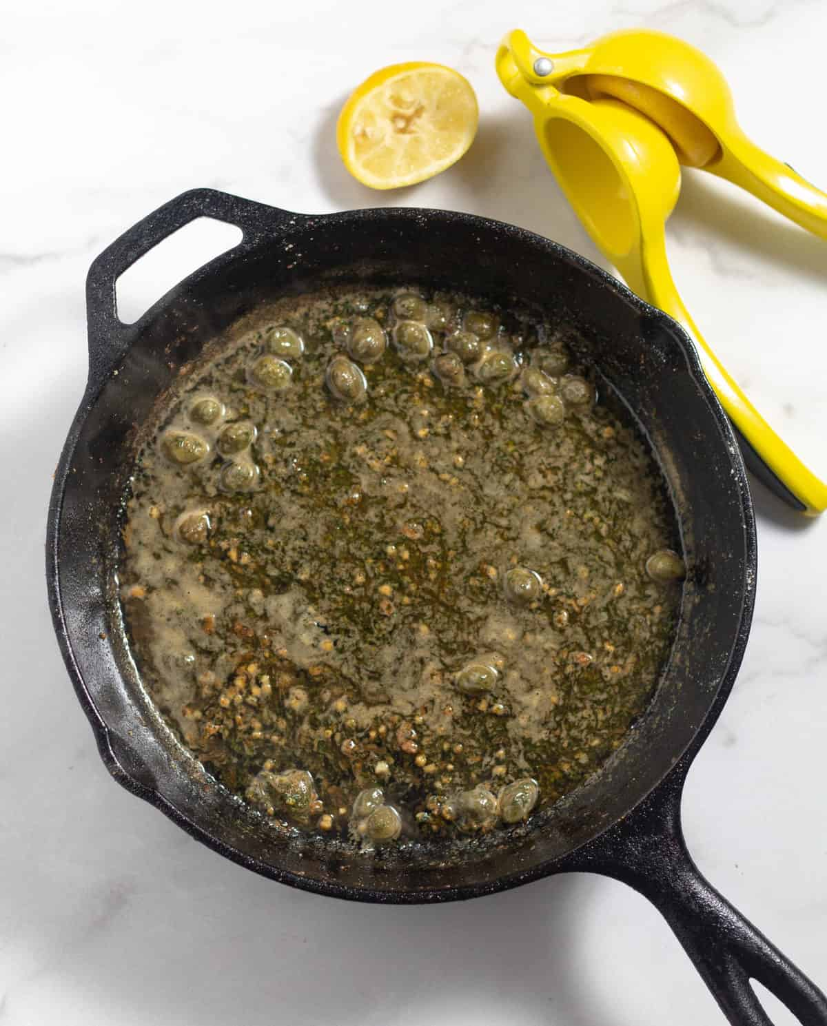 overhead shot of piccata sauce in cast iron skillet