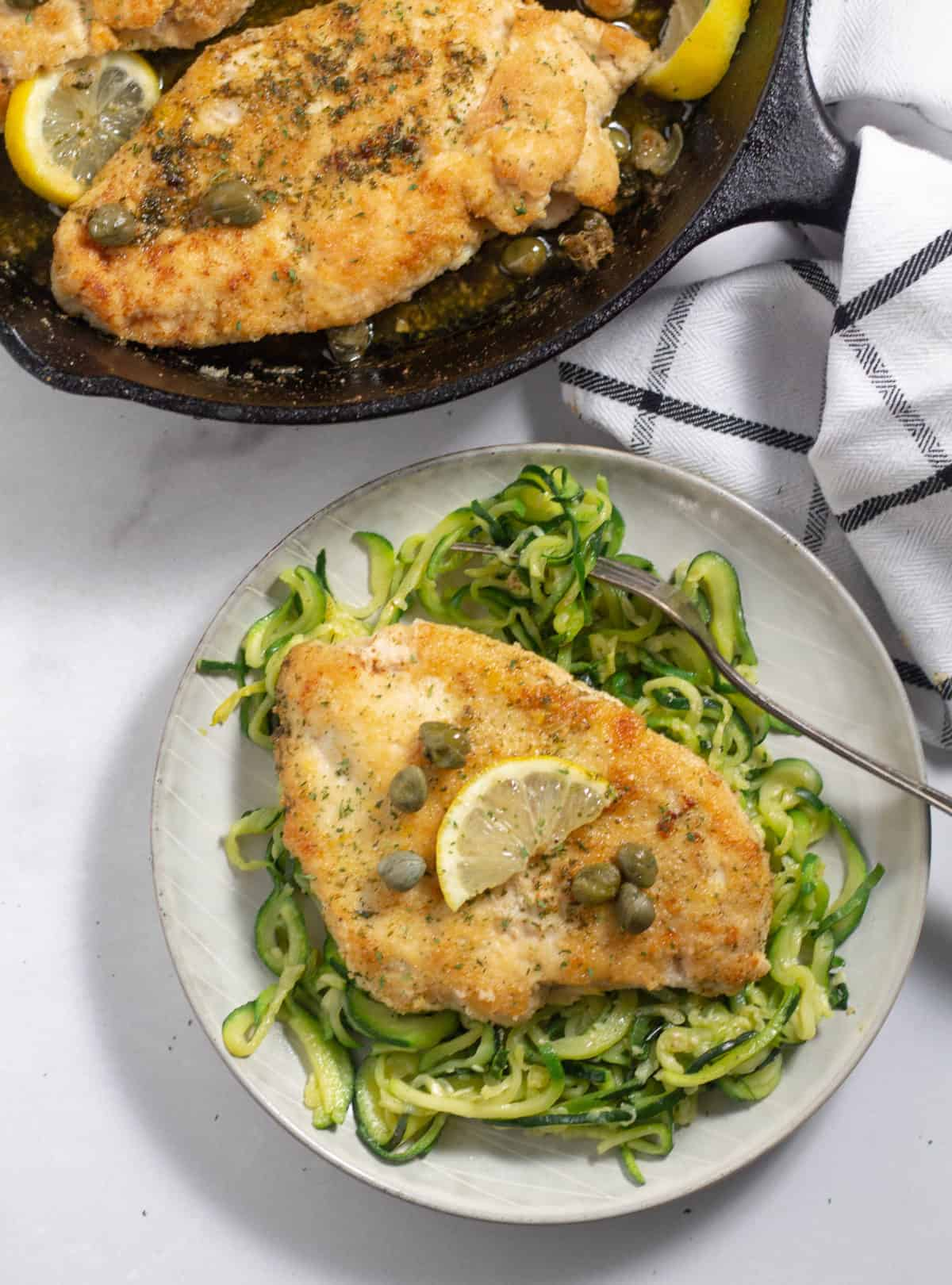 Chicken Piccata on a plate over zucchini noodles