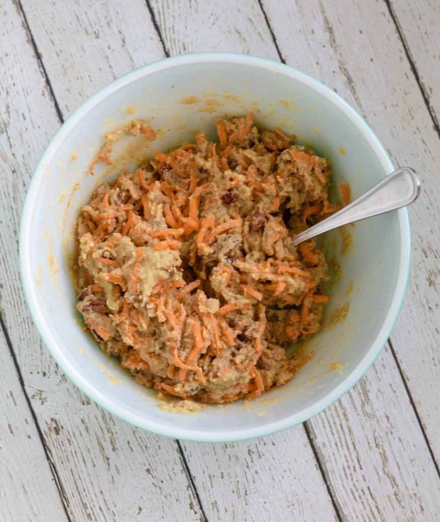 cake cake batter with sliced carrots mixed together in bowl