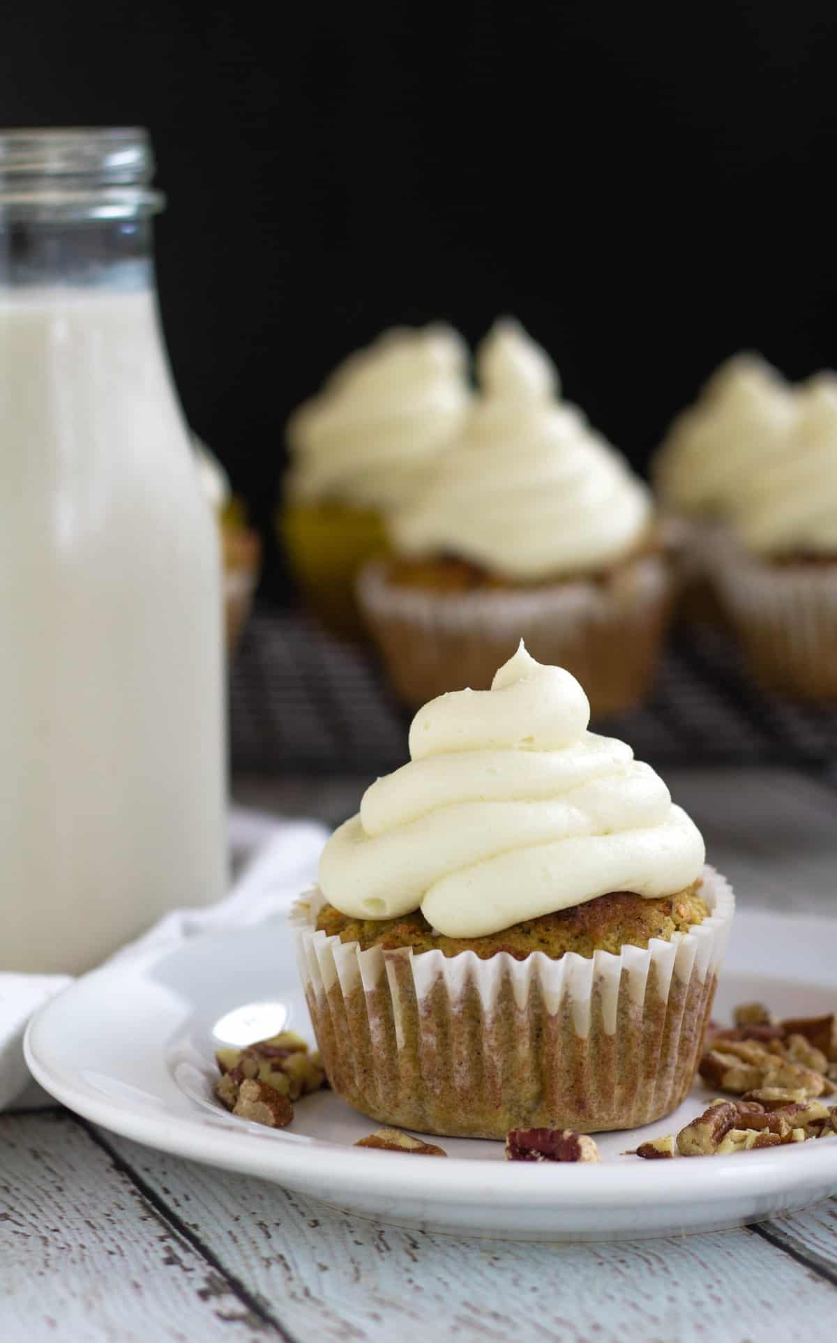 frosted cupcake on small white plate with milk and carrot cake cupcakes in the background
