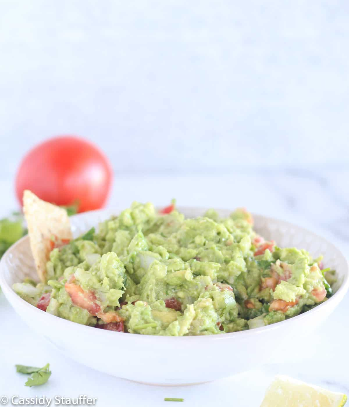 Sideshot of guacamole in white bowl with corn chips