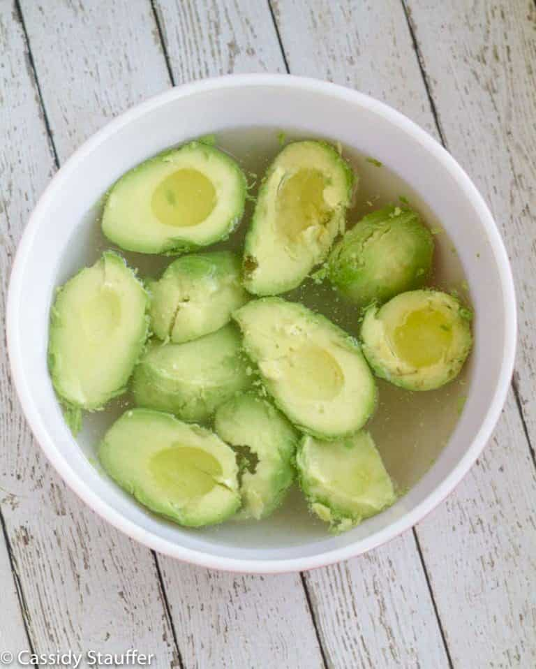 Avocado halves soaking in a bowl of warm saltwater