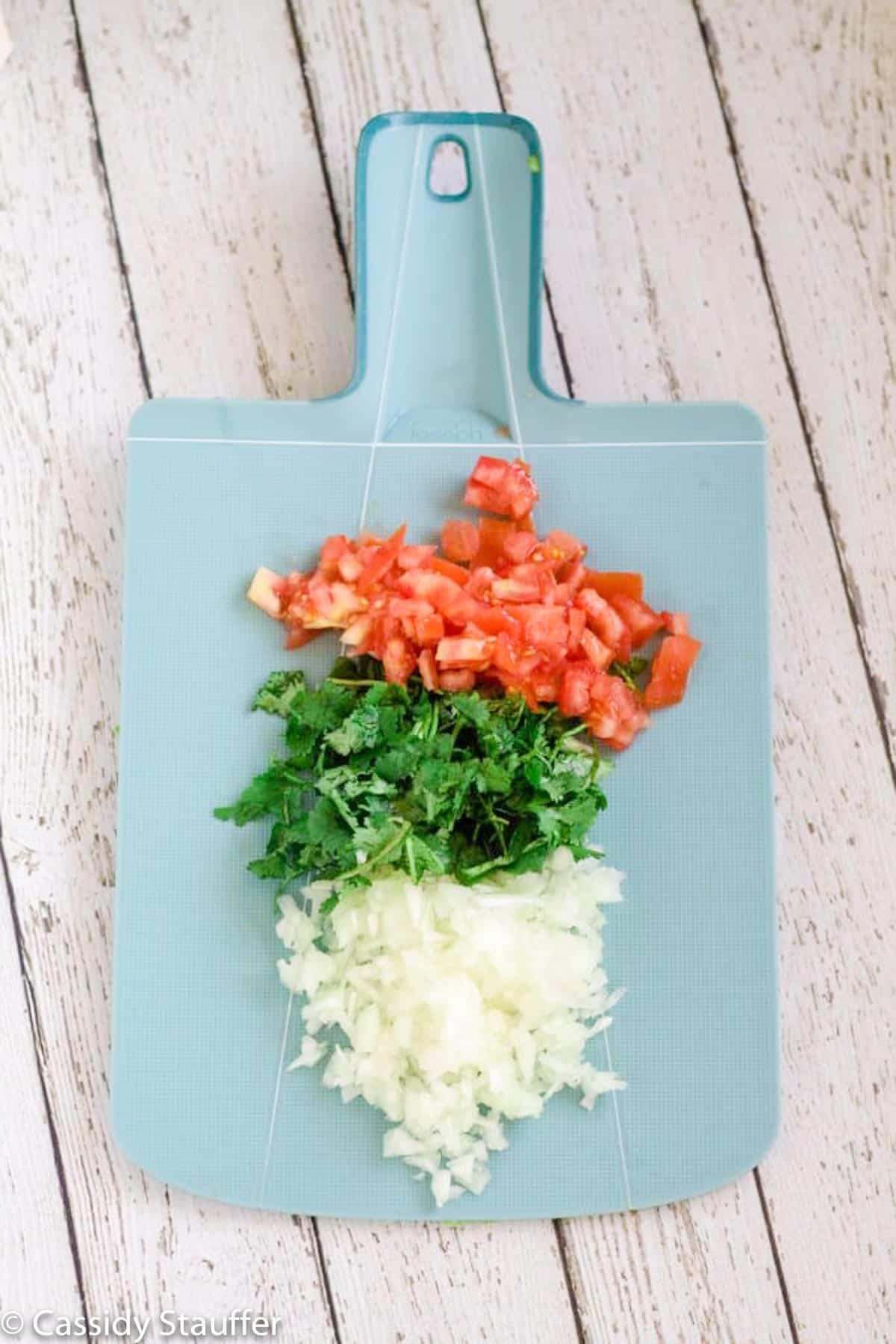 Chopped onion, cilantro, and tomatoes on a cutting board