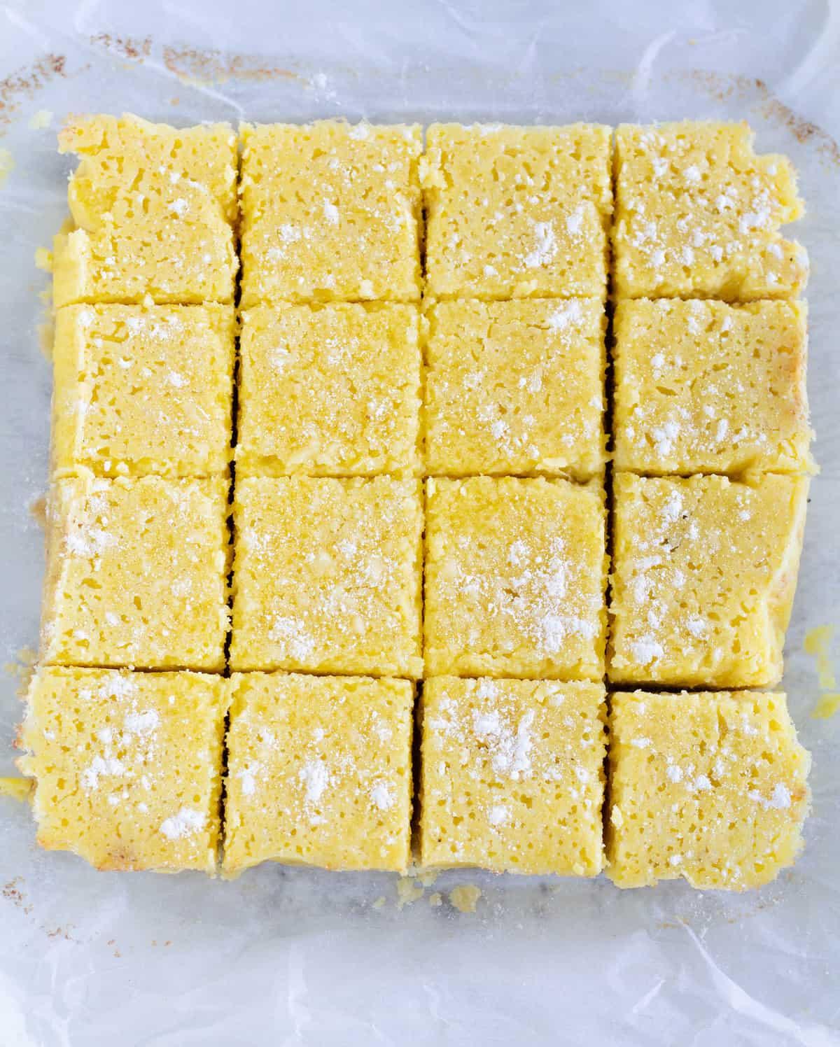 overhead shot of lemon bars cut into squares on parchment paper