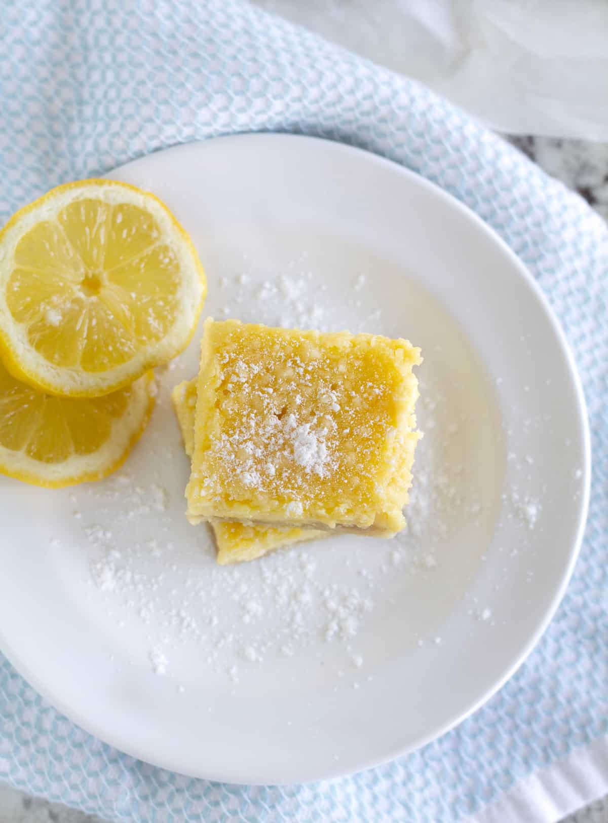 overhead shot of 2 keto lemon bars stacked on top of each other on white plate with lemon slices