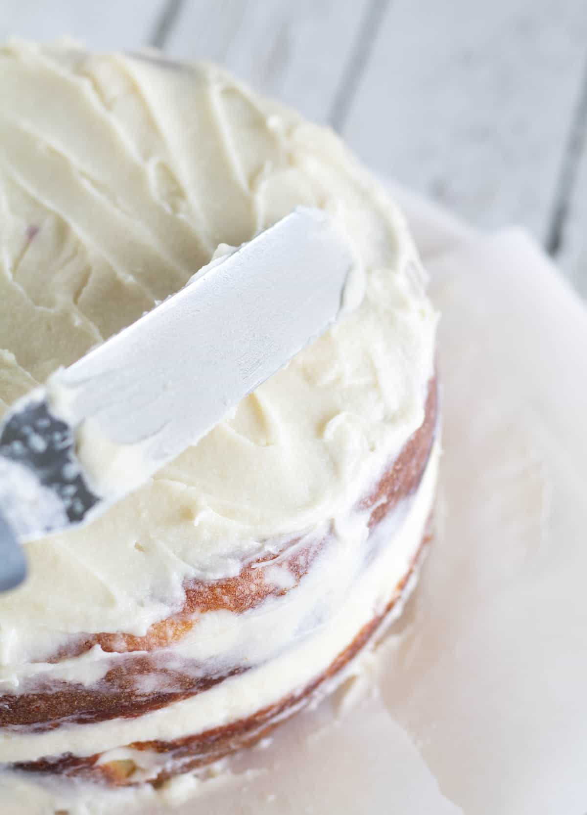 Using a spatula to even out the top edge of the naked cake