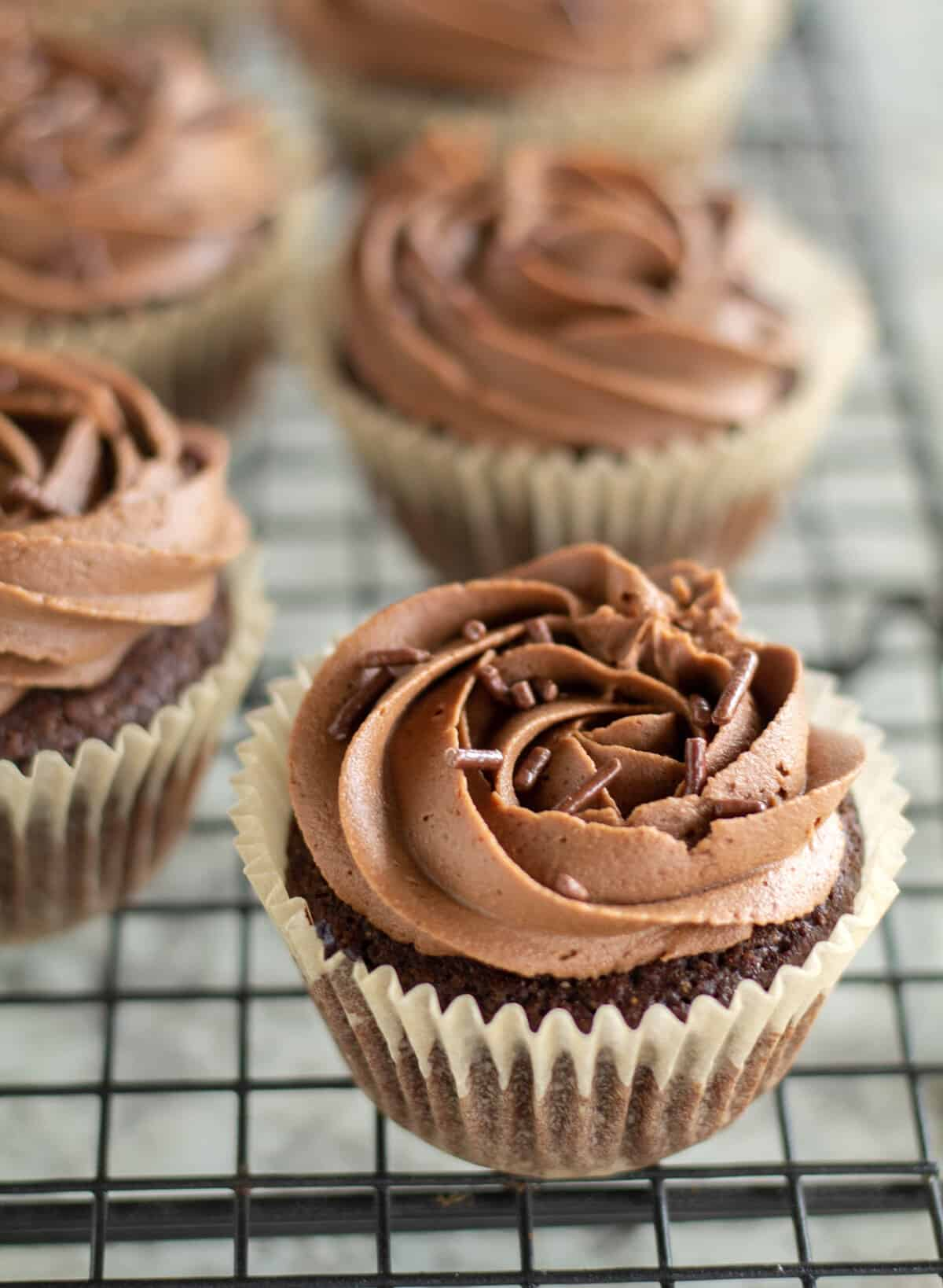 cupcakes with chocolate frosting on cooling rack with sprinkles