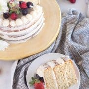 slice of cake on white plate with berries and cake in the background