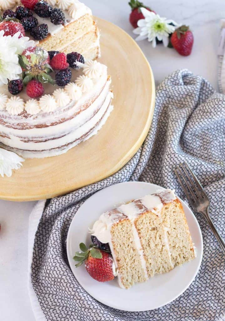 slice of cake with berries on a plate next to cake on stand
