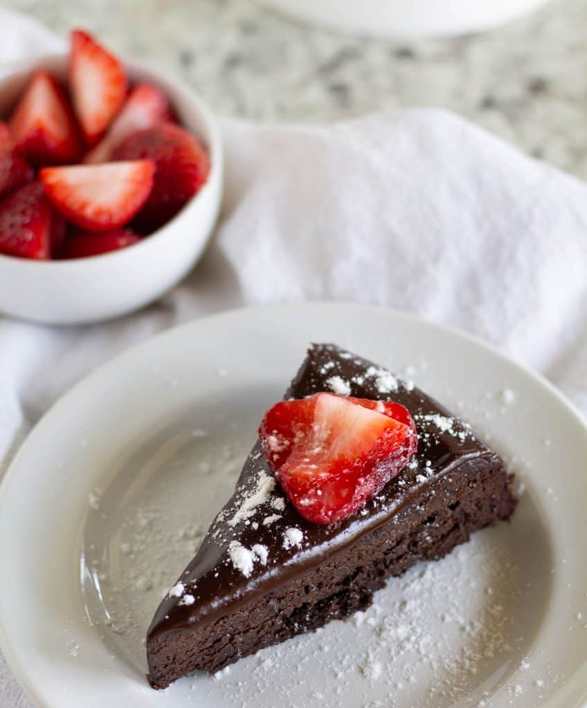 Keto Flourless Chocolate Cake With Vegan Ganache on white plate with strawberries on top