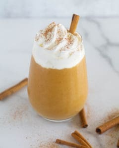 keto, paleo, & vegan pumpkin smoothie in clear glass with whipped cream and cinnamon sticks