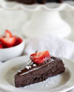 flourless chocolate cake on white plate with strawberries