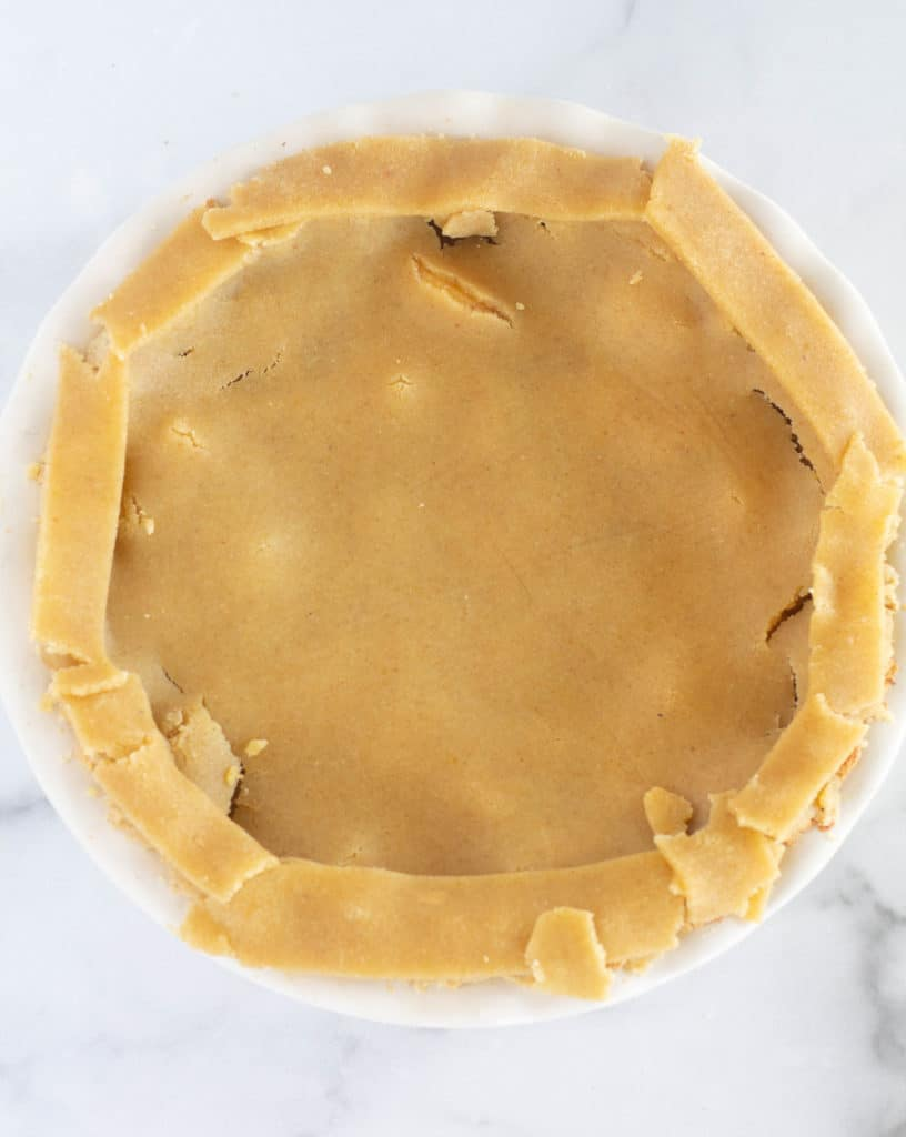 adding strips of crust to the edges of the pie