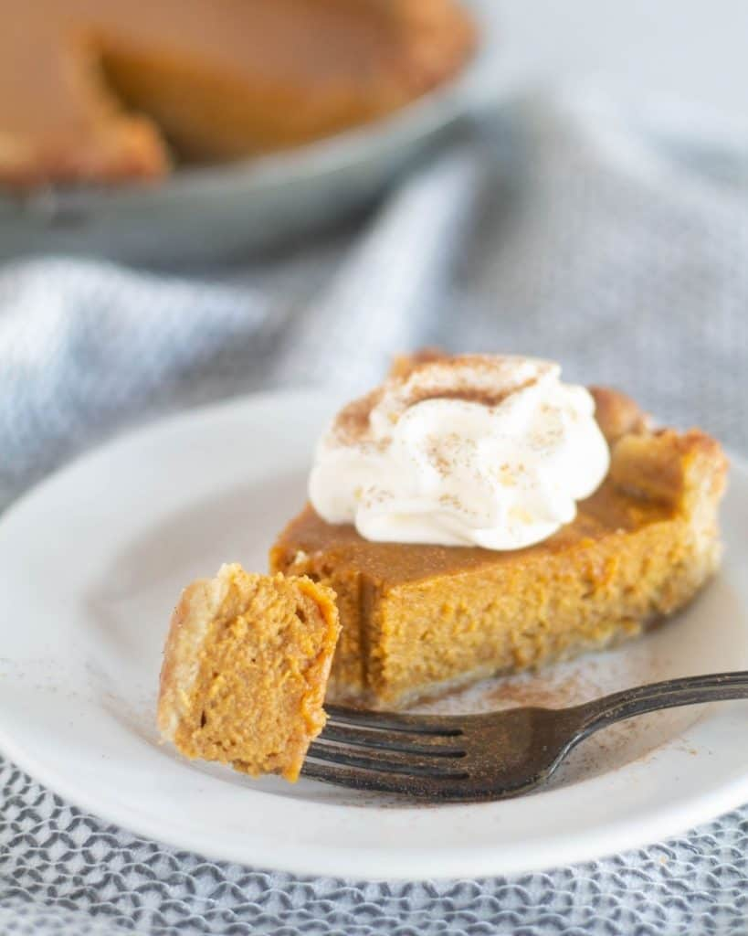 slice of pumpkin pie on plate with bite on fork