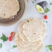 cassava tortillas on countertop with tomatoes and avocado