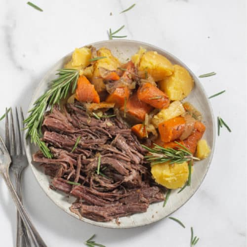 roast on a plate with carrots and potatoes
