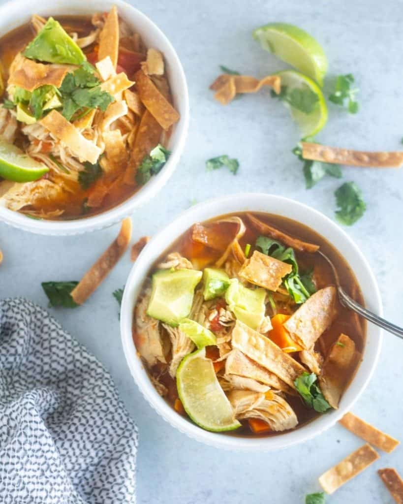 overhead shot of tortilla sop in bowls with garnishes