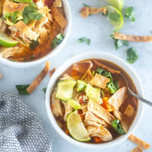 tortilla soup in white bowl with garnishes
