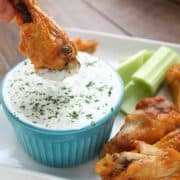 dipping a chicken wing into ranch dressing