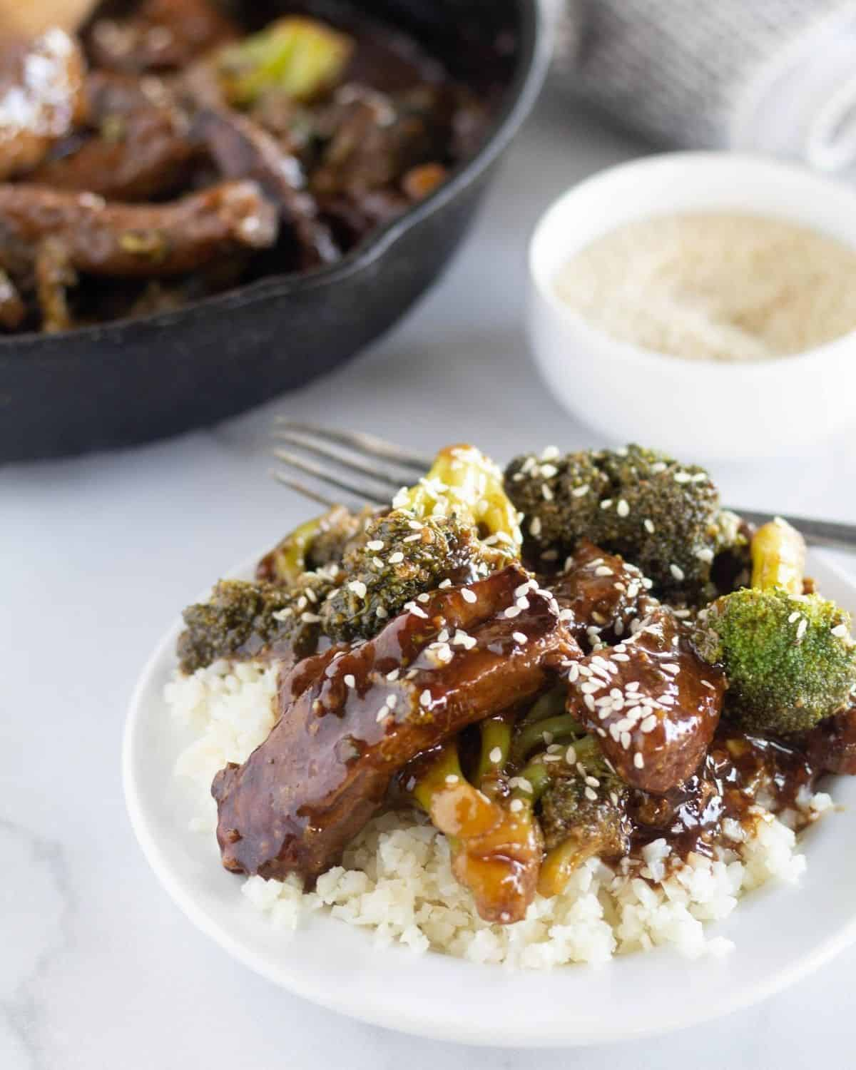 beef and broccoli on plate over cauliflower rice