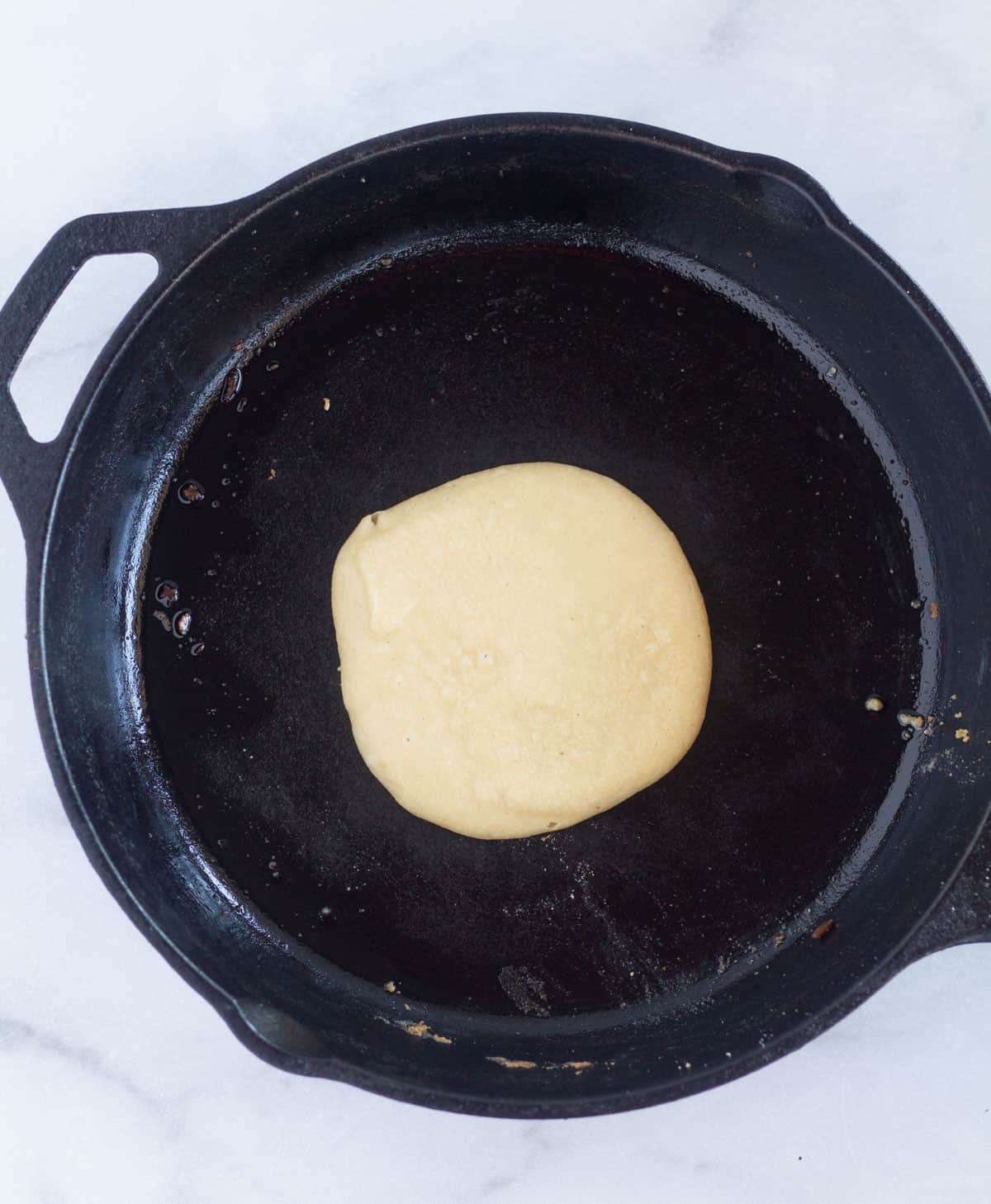 pancake cooking in cast iron skillet