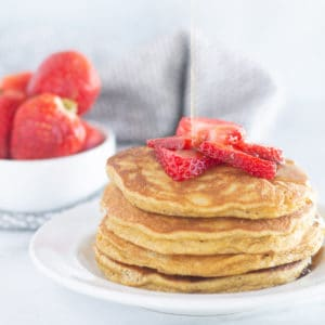 pancakes stacked on white plate with strawberries