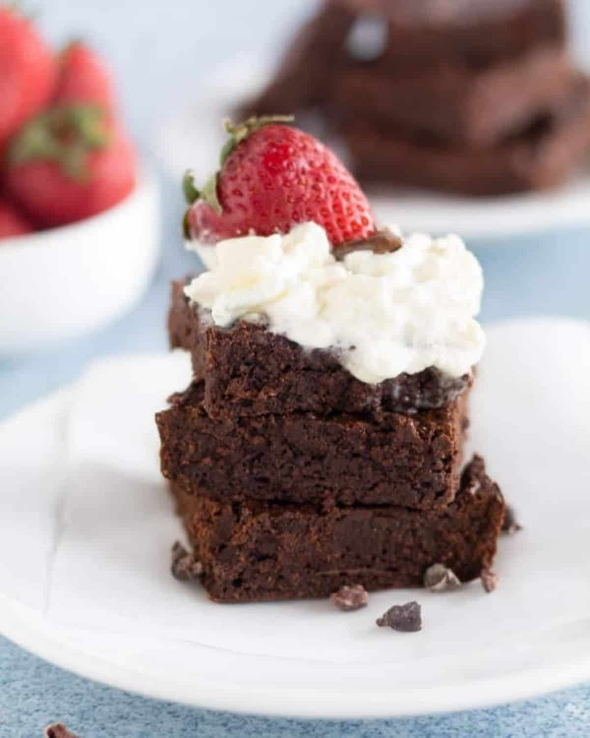brownies stacked on white plate with cream and strawberries