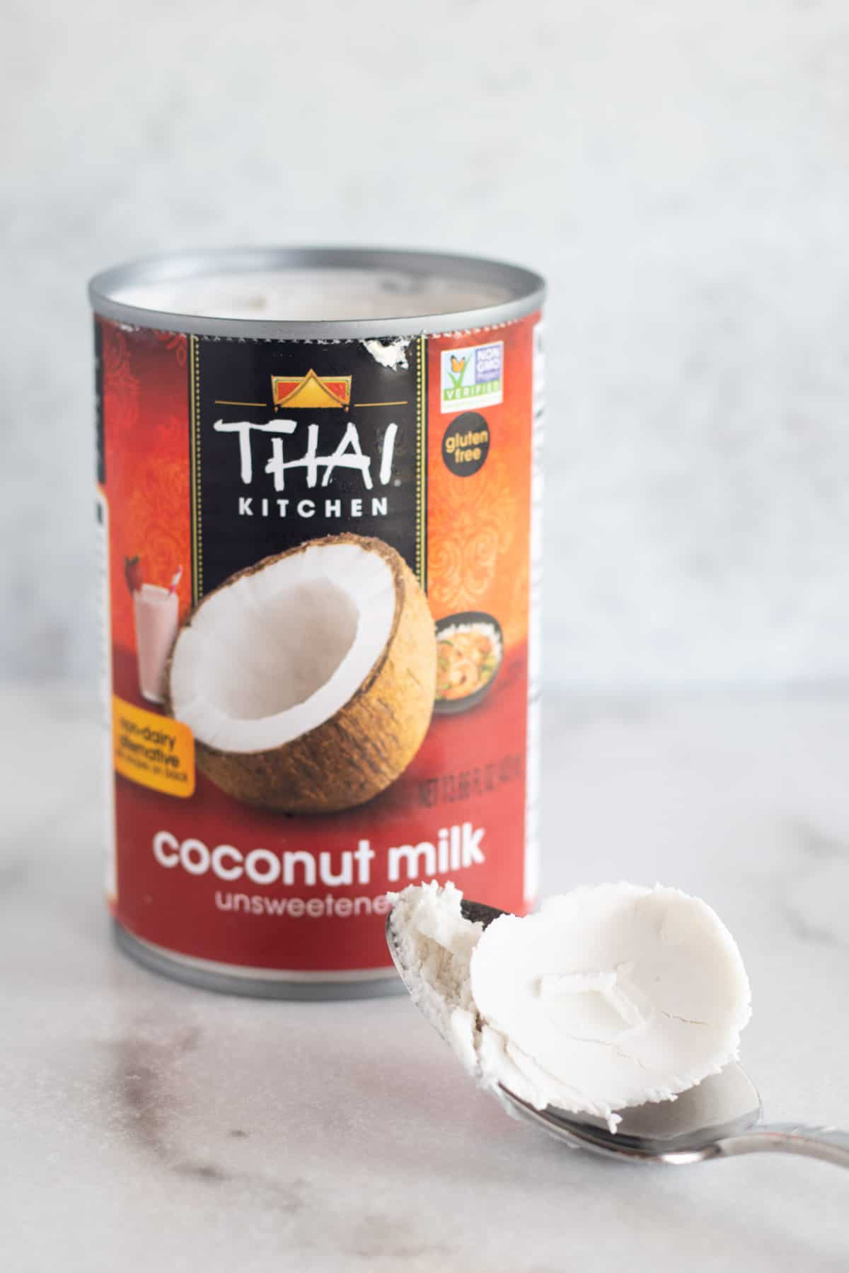 scooping cream out of a can of coconut milk