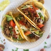 3 tacos on a small plate with garnishes