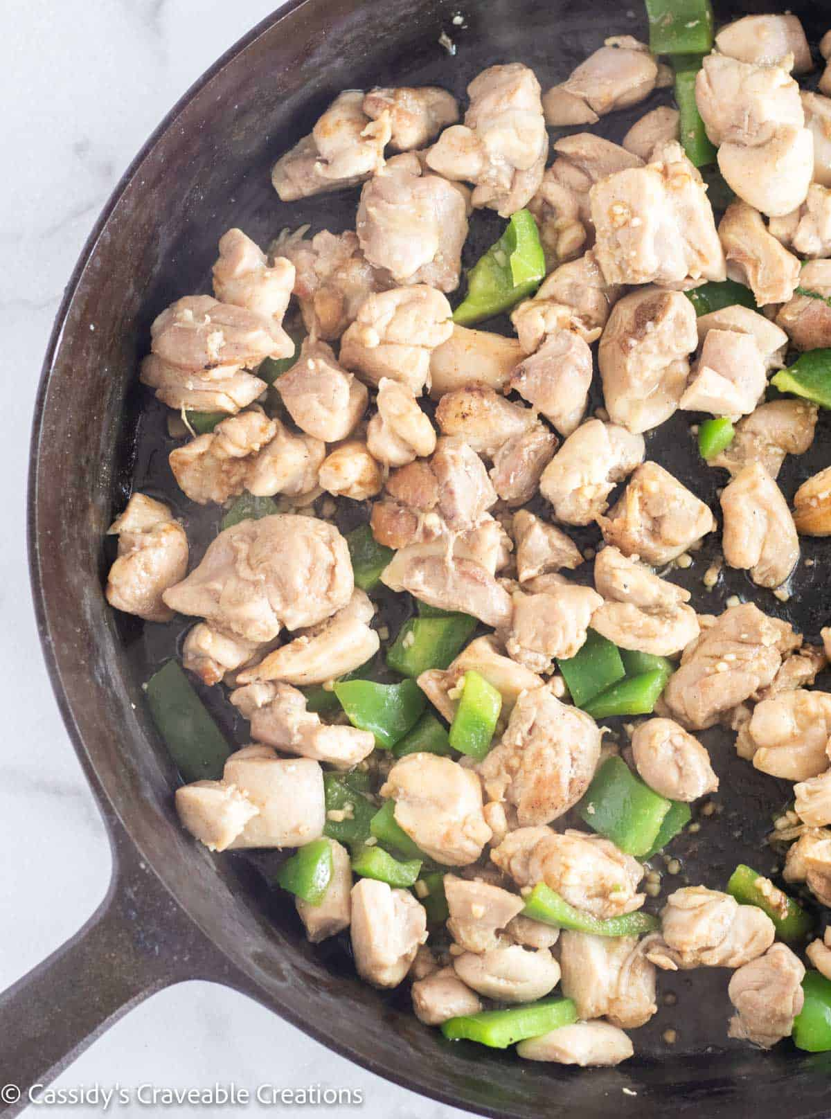 chicken with bell pepper, garlic, and ginger in skillet