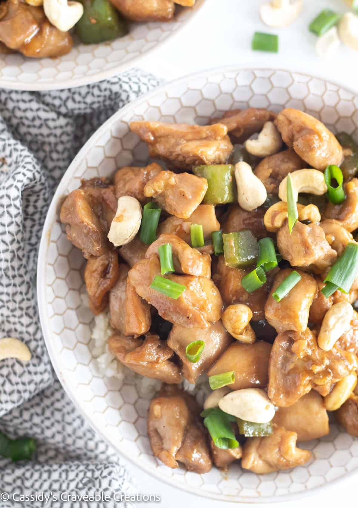 overhead shot of cashew chicken in a bowl over cauliflower rice