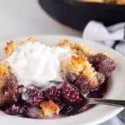 scooping a bite of cobbler from a plate with whipped cream