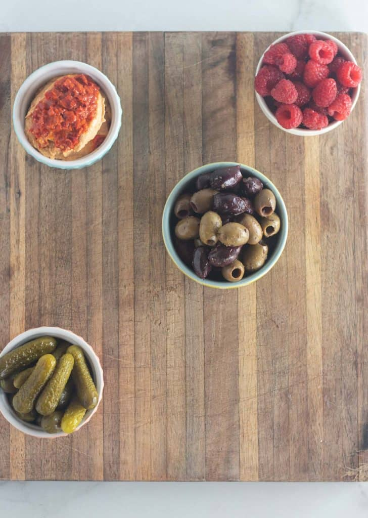 bowls with garnishes on cutting board