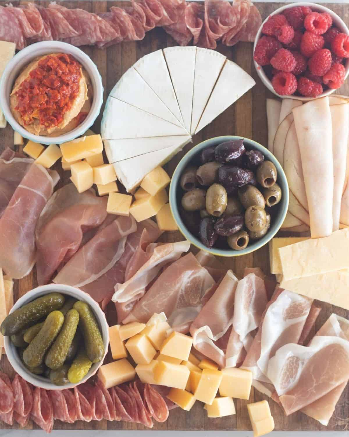 meats and cheeses arranged on board