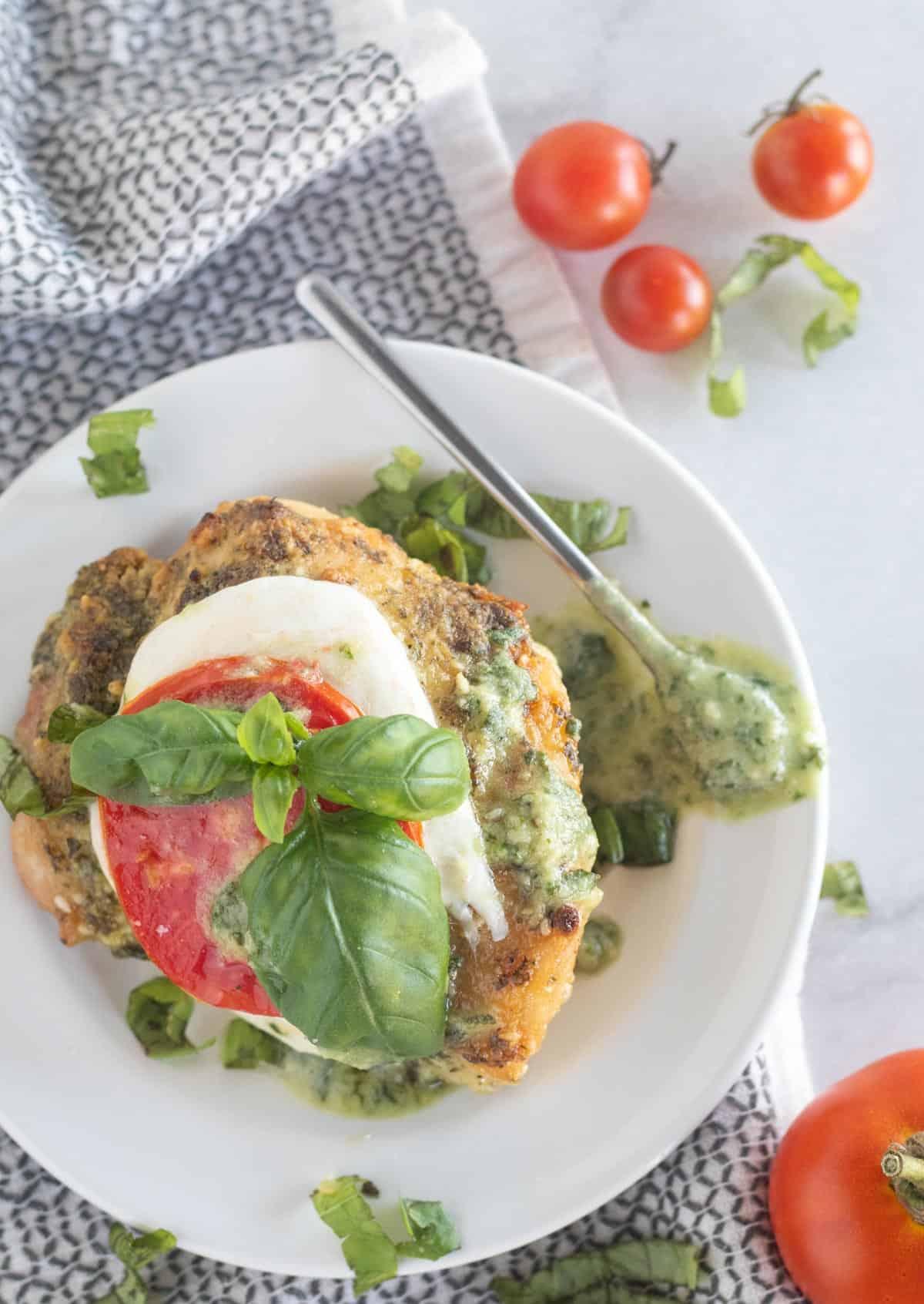 overhead shoto of pesto chicken on plate with mozzarella, tomato, and basil